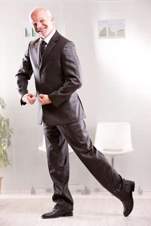 foolish: Goofy businessman pretending weightlifting  with his arms and foolish face