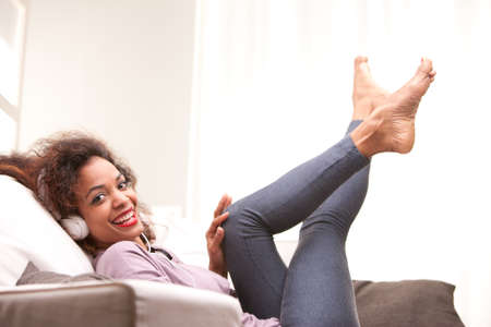 beautiful afroamerican woman on a sofa listenint to the music with her headphones Stock Photo - 27548016