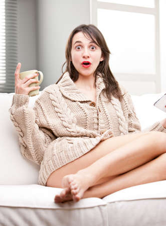 sagacious: astonished girl on a sofa with a mug and a tablet Stock Photo