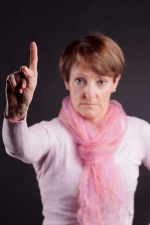 mature woman with a raised hand with index up denying or imposing photo