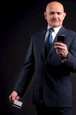 an old businessman with a credit card and a mobile hphone making purchases online Stock Photo - 29009741