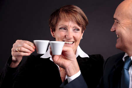 a smiling elderly couple holding up two cups of italian espreso coffee and smiling each other Stock Photo
