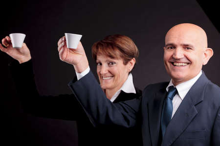 a smiling elderly couple holding up two cups of italian espreso coffee and smiling each other photo