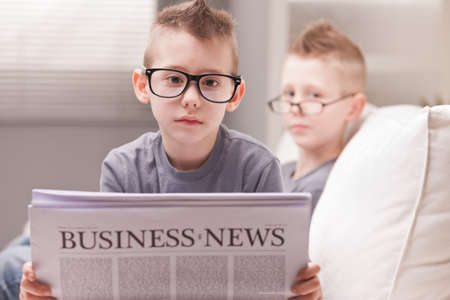 two little boys reading on newspapers or digital devices photo