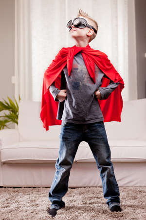 a little kid playing as a red cloak serious superhero photo