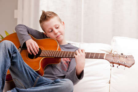 living room boy: little boy playing guitar on a sofa in his living room