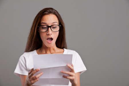 femme bouche ouverte: jeune femme brune se rend compte que quelque chose d'extraordinaire s'est produit à lire une lettre ou un document blanc Banque d'images