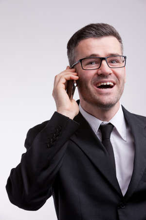 an elegant dressed man with a pair of eyeglasses happy and talking his mobile phone photo