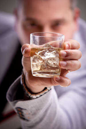 glass of alcoholic drink in mans hand photo