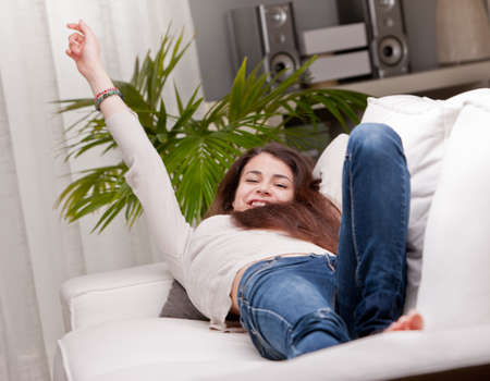 lolita: girl happily waking up on her sofa and yawning while stretching