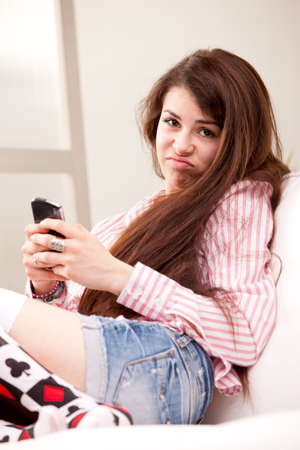 young girl holding a grouch against mobile phone that disappointed her