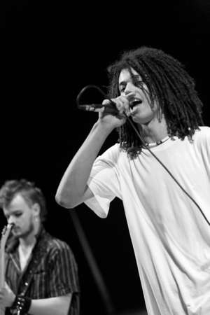 live action: rock singer with rasta hair performing live on stage OUT LOUD Stock Photo