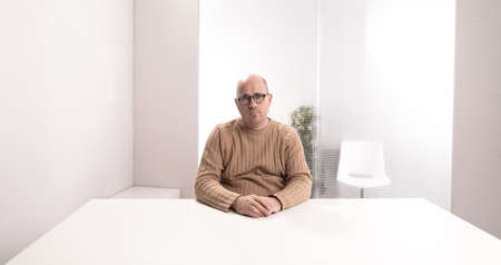 sad bald plump man with glasses in an empty office waiting