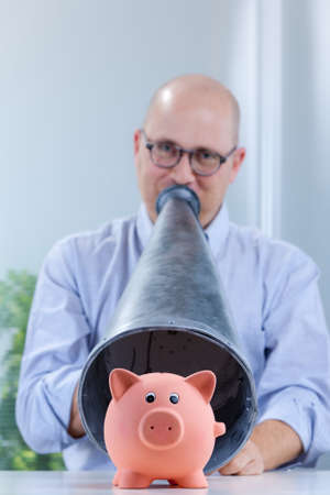 piggy bank on the foreground and shouting man with a megaphone on the background Stock Photo