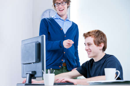 two faced: a couple of young office workers smiling at a screen
