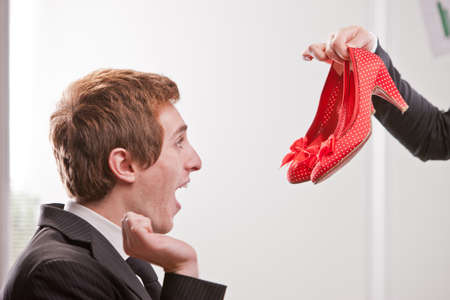 fop: A fop boy showing an excessive happiness facing a pair of red shoes with medium heels