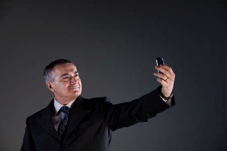 inseparable: A senior manager using successfully his inseparable smartphone agenda and calendar, now taking a selfie