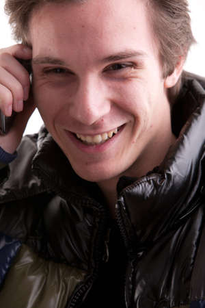 anorak: a young man on anorak speaking on his mobile phone happily