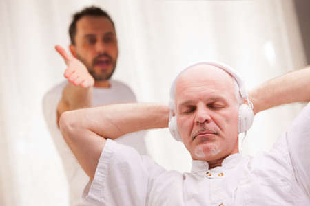 lazybones: one friend complains to the other one because he listens to music and does nothing else Stock Photo