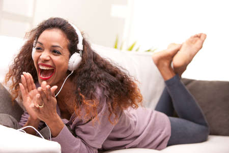 of african descent: african american woman singing on a sofa wearing white headphones Stock Photo