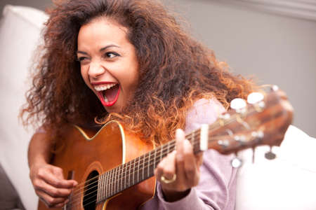 afroamerican woman singing and playing guitar on her sofa in her living room photo