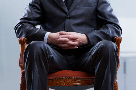 old boss or politician sitting on a chair he wont leave