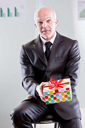 elegant business man: an elegant business man has a gift in his hands