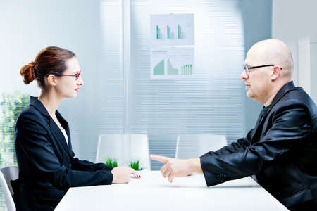 enmity: business man and business woman discussing facing each other in a polite discussion