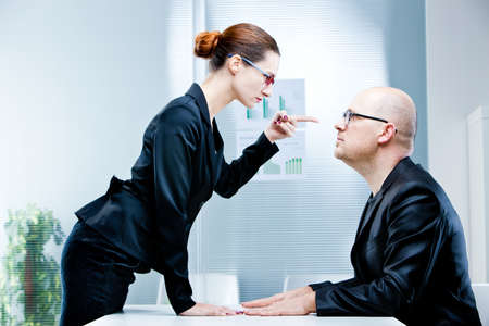 business woman pointing out a business man reproaching him at work in an office photo