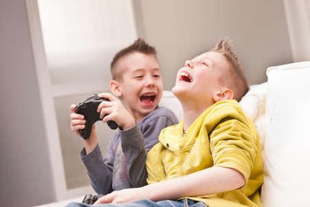 hermanos jugando: dos ni�os peque�os que tienen un mont�n de diversi�n con los juegos de video Foto de archivo