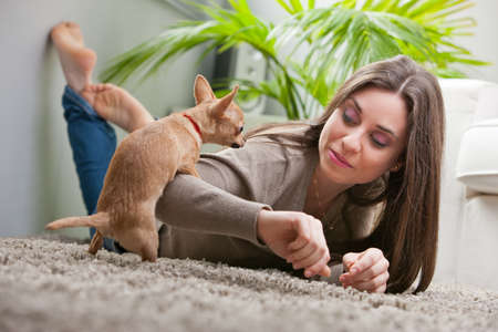 animal sex: young beautiful woman loving her puppy in her living room