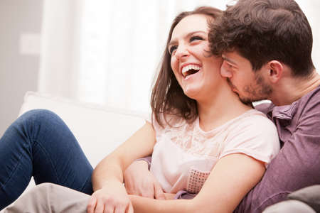 arousal: love understanding are what this couple shows off while lying on their living room sofa embracing and enjoying