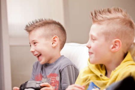 kids playing video games: little brothers smiling at their mother (not visible) Stock Photo