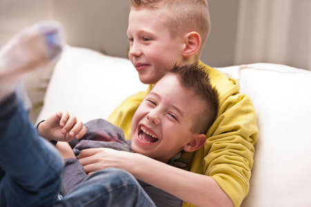 tickling: two little boys maybe friends or brothers two little boys laughing about tickling