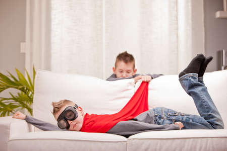 elementary age boys: kids playing superheros on a sofa but one of them is not enjoying the game very much Stock Photo