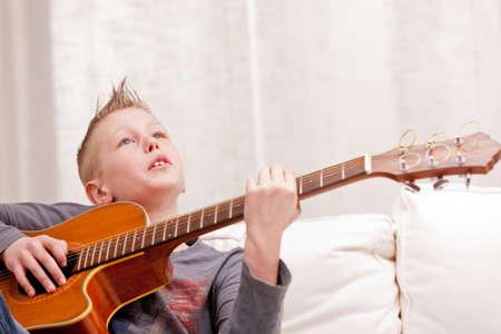 boy playing guitar: little boy playing guitar on a sofa in his living room