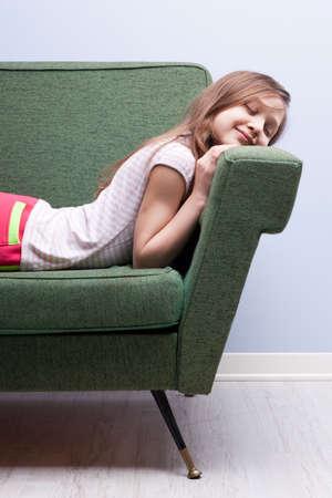 어린 소녀: little girl softly sleeping like a cat on a green sofa 스톡 사진