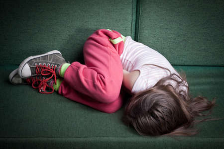 little girl curled up in fetal position on a couch protecting herself from danger or cold photo
