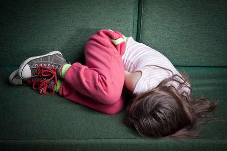 niño llorando: niña acurrucada en posición fetal en un sofá que se protege contra el peligro o el frío