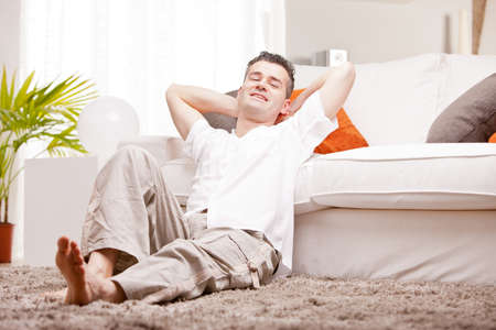 relaxed man having finally his time off in his living room and his beloved  couch Stock Photo
