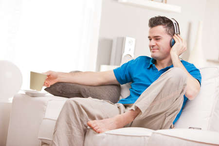relaxed man having finally his time off in his living room and his beloved  couch while he listens to music in his earphones