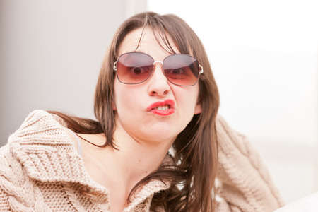 funny faces: woman with sunglasses making funny faces (perplexed)