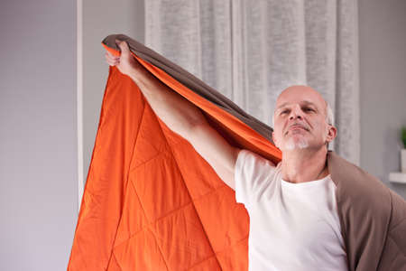 superpowers: man pretending to be a superhero in his living room using his quilt as a cloak