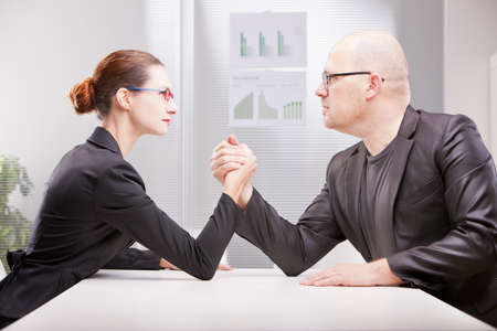 challenging sex: busineee woman facing business man and starting to perform an arm wrestling to decree whos best