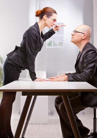challenging sex: woman towering on a business man standing her outburst Stock Photo