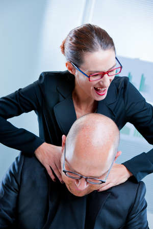 tormented: business woman relishing his sadism against his tormented colleague Stock Photo