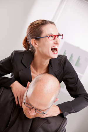 sadistic: business woman driven insane strangling a business man Stock Photo