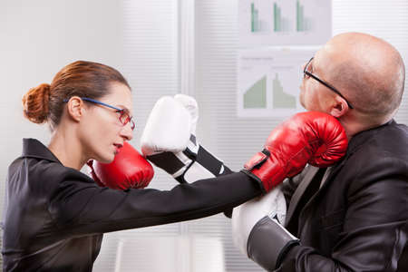 challenging sex: business woman hitting a business man in a box match with a right jab