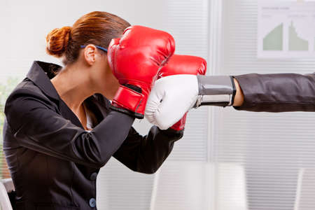 challenging sex: boxing business woman defending effectively from a punch