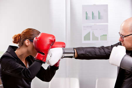 challenging sex: business man trying to punch a business woman in a box match Stock Photo